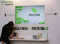 A counter promoting WeChat, a product of Tencent, on reading books for the blind, is displayed at a news conference announcing the company's results in Hong Kong March 18, 2015. Tencent Holdings Ltd , China's biggest social network and online entertainment firm, posted a 51 percent gain in fourth-quarter net income, missing estimates, as sharing and content costs took a bite out of healthy revenue growth.   REUTERS/Bobby Yip