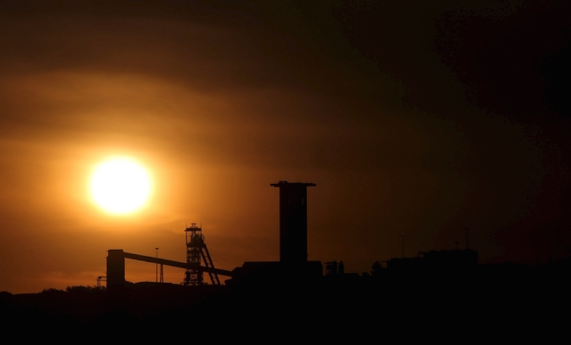 """The sun sets behind a shaft outside the mining town of Carletonville, west of Johannesburg, July 7 2015. South African gold producers said on Tuesday that union wage demands were """"unaffordable"""" and could add 16.5 billion rand ($1.3 billion) to the sector's wage bill.The producers, which include AngloGold Ashanti, Sibanye Gold and Harmony Gold, said in a statement that the industry's total wage bill in 2014 was 23.5 billion rand. REUTERS/Siphiwe Sibeko"""
