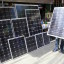 A vendor holds a piece of solar panel to attract buyers at a stall in Manila July 13, 2015. Solar companies will push the Philippine government to quadruple the size of an incentive scheme for suppliers of the renewable energy and to speed up project approvals, as the country grapples with precarious electricity supply. REUTERS/Romeo Ranoco