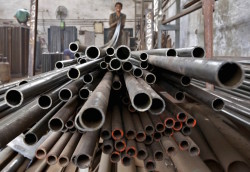 A worker stacks steel pipes in the western Indian city of Ahmedabad in this November 4, 2014 file photo. Any nuclear deal between Iran and six world powers loosening sanctions against Tehran could flood an oversupplied oil market with more fuel, yet sectors like cement and steel would see a rise in demand as the country works to revitalise its economy. Officials involved in ongoing negotiations said on Sunday they were close to a deal that would bring sanctions relief in exchange for curbs to Tehran's atomic programme, although no agreement was expected before July 13, 2015. REUTERS/Amit Dave/Files