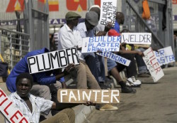 Men hold placards offering temporal employment services in Glenvista, south of Johannesburg, October 7, 2010. REUTERS/Siphiwe Sibeko