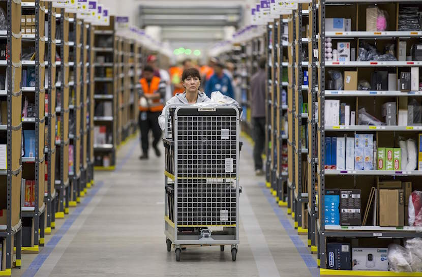A worker puts together orders at the Amazon logistics center in Brieselang, in this November 11, 2014 file photo. Amazon.com Inc's shares surged more than 20 percent in early trading July 24, 2015, adding more than $46 billion to the compnay's market value, after strong growth in the e-commerce giant's cloud business drove a surprise quarterly profit.  REUTERS/Hannibal/Files