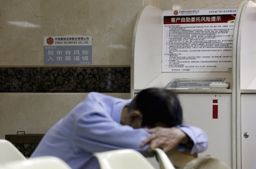 """An investor takes a nap next to a sign (L) that reads """"the stock market is risky, be prudent in investment"""" at a brokerage house in Beijing, August 26, 2015. Asian shares struggled on Wednesday as investors feared fresh rate cuts in China would not be enough to stabilise its slowing economy or halt a stock collapse that is wreaking havoc in global markets. REUTERS/Jason Lee"""