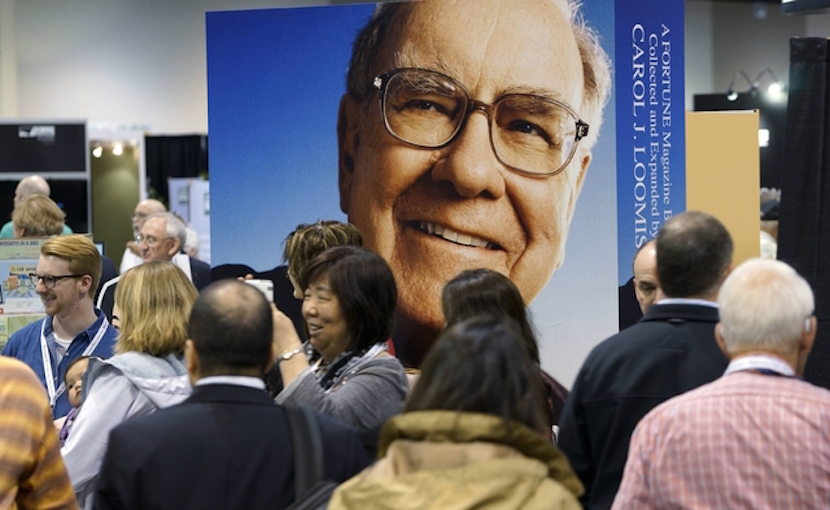 Berkshire Hathaway shareholders walk by Berkshire CEO Warren Buffett's image at the shareholder's shopping day in Omaha, Nebraska in this May 1, 2015 file photo. Warren Buffett is paying a hefty price for the biggest bet of his career as his Berkshire Hathaway Inc has agreed to buy Precision Castparts Corp, valuing the maker of aerospace and other parts at $32.3 billion.    REUTERS/Rick Wilking/Files