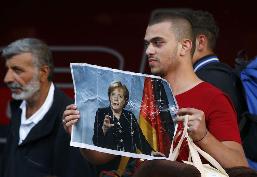 A migrant holds a portrait of German Chancellor Angela Merkel after arriving to the main railway station in Munich, Germany September 5, 2015. Austria and Germany threw open their borders to thousands of exhausted migrants on Saturday, bussed to the Hungarian border by a right-wing government that had tried to stop them but was overwhelmed by the sheer numbers reaching Europe's frontiers. REUTERS/Michael Dalder