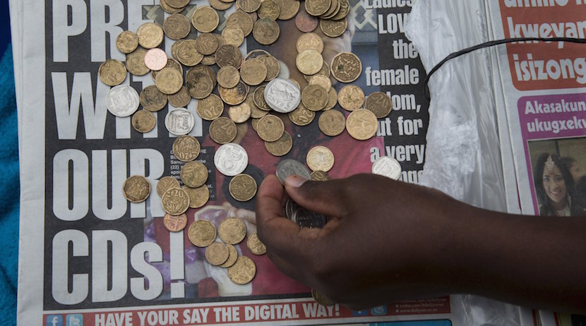 A newspaper vendor counts out change for a customer in Durban, September 8, 2015. REUTERS/Rogan Ward