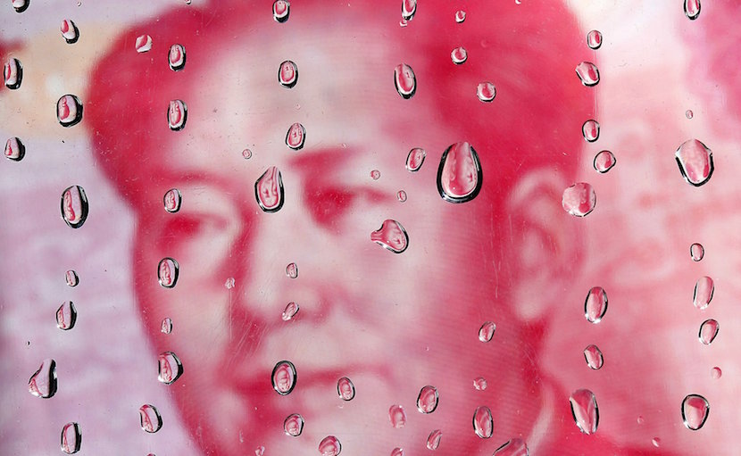 A portrait of former Chinese leader Mao Zedong on a yuan banknote is reflected in water droplets in this picture illustration taken in Taipei in this October 8, 2010 file photo. China's central bank plans to tighten rules on trading of currency forwards from October, sources with direct knowledge of the matter told Reuters, in a move to curb speculation and volatility after a shock devaluation of the currency in August 2015. REUTERS/Nicky Loh/Files