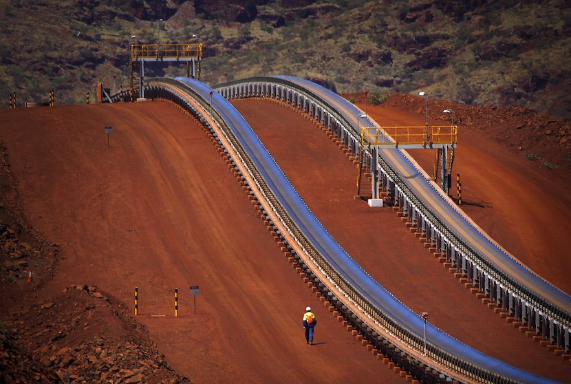 A worker walks near conveyer belts loaded with iron ore at the Fortescue Solomon iron ore mine located in the Valley of the Kings, around 400 km (248 miles) south of Port Hedland in the Pilbara region of Western Australia December 2, 2013. Shares in Australia's Fortescue Metals Group jumped 9 percent on August 5, 2015, boosted by a report that China's Hebei Iron & Steel Group and Tewoo Group could invest in its infrastructure and mining assets. The iron ore miner's term loan traded higher on Tuesday, also lifted by speculation over a potential tie in. REUTERS/David Gray