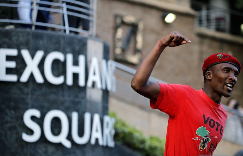 A member of South Africa's left-wing Economic Freedom Fighters (EFF) gestures outside the Johannesburg Stock Exchange (JSE) in Sandton, October 27, 2015. Thousands of South Africa's Economic Freedom Fighters (EFF) protested outside the Johannesburg stock exchange on Tuesday in pursuit of working class votes for the radical leftist party ahead of municipal elections next year.The EFF, led by firebrand Julius Malema, is looking to use the momentum built from student demonstrations last week to increase the pressure on President Jacob Zuma's African National Congress (ANC), the anti-apartheid party of Nelson Mandela. REUTERS/Siphiwe Sibeko