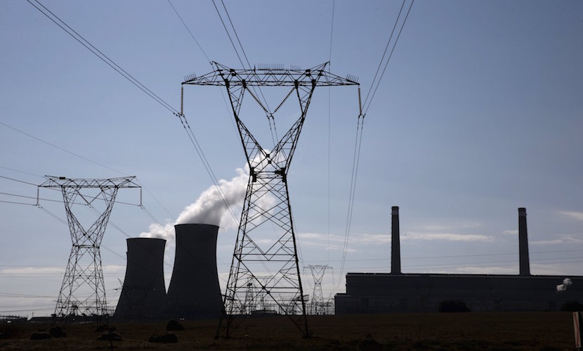 Electricity pylons are seen near Arnot Power Station's cooling towers, east of Middelburg in Mpumalanga province, September 8 2015. South Africa's struggling power utility Eskom has marked 30 straight days without imposing rolling power cuts, providing a spark of hope to an economy on the brink of recession. REUTERS/Siphiwe Sibeko