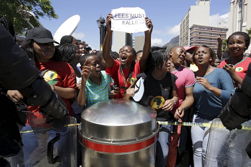Students protest over planned increases in tuition fees outside South Africa's Parliament in Cape Town, October 21, 2015. Riot police fired tear gas and stun grenades on Wednesday at hundreds of protesting students who stormed the parliament precinct in Cape Town to try to disrupt the reading of Finance Minister Nhlanhla Nene's interim budget. REUTERS/Mark Wessells
