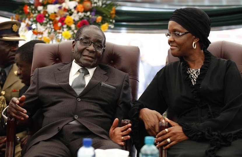 Zimbabwe President Robert Mugabe speaks to his wife Grace during the funeral of his sister, Bridget, in the village of Zvimba