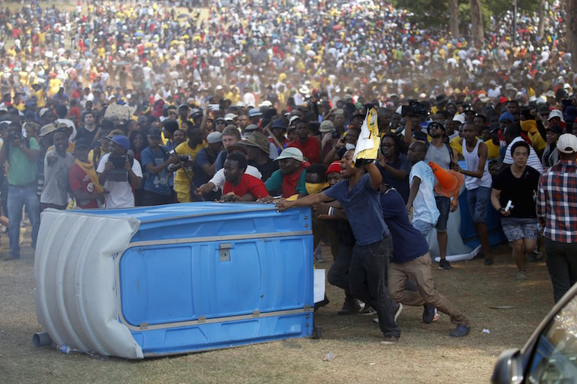 Protesters push a portable loo before burning it during a protest over planned increases in tuition fees outside the Union building in Pretoria, South Africa October 23, 2015. South African police fired stun grenades at students who lit fires outside President Jacob Zuma's offices following a week of protests, the first signs of the post-apartheid 'Born Free' generation flexing its muscle. REUTERS/Siphiwe Sibeko