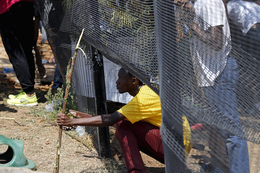 A demonstrator looks through a fence during a protest over planned increases in tuition fees outside the Union building in Pretoria, South Africa October 23, 2015. South African police fired stun grenades at students who lit fires outside President Jacob Zuma's offices following a week of protests, the first signs of the post-apartheid 'Born Free' generation flexing its muscle. REUTERS/Siphiwe Sibeko