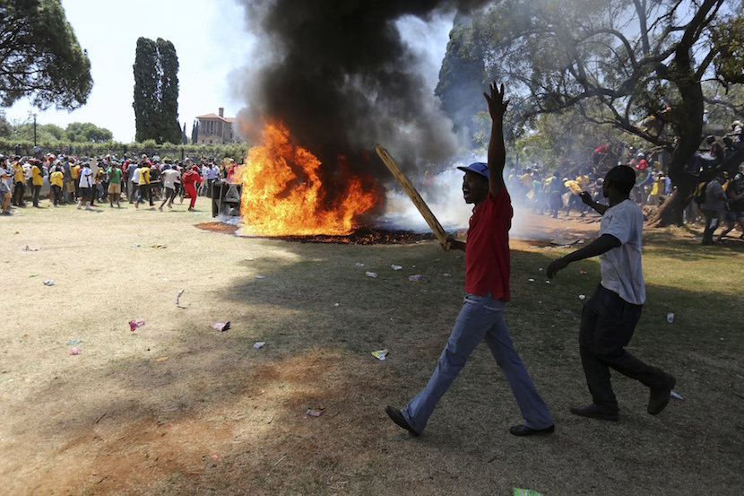 A demonstrator gestures in front of a burning portaloo during a protest over planned increases in tuition fees outside the Union building in Pretoria, South Africa October 23, 2015. South African police fired stun grenades at students who lit fires outside President Jacob Zuma's offices following a week of protests, the first signs of the post-apartheid 'Born Free' generation flexing its muscle. REUTERS/Siphiwe Sibeko