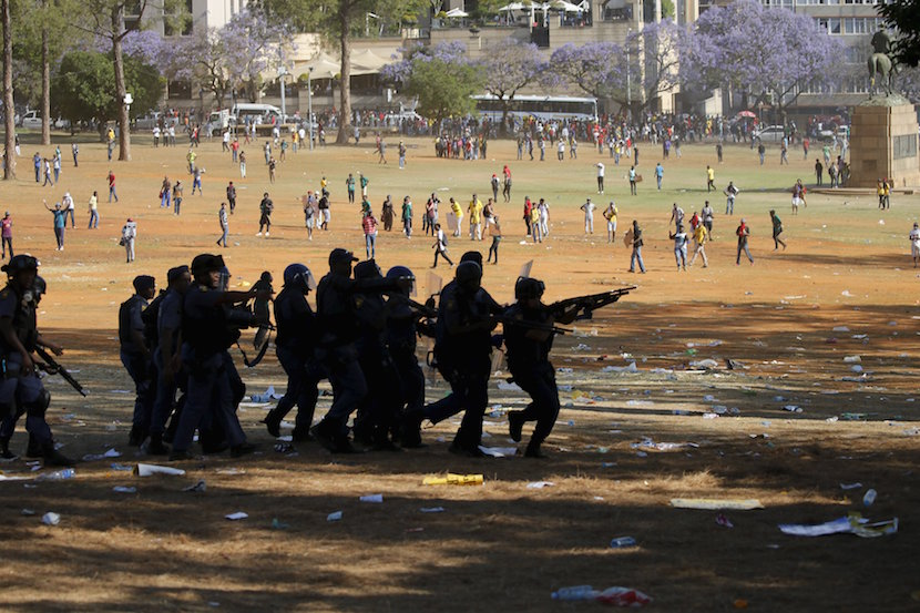Protesters run as they are dispersed by police officers during a protest over planned increases in tuition fees outside the Union building in Pretoria, October 23, 2015. South African police fired stun grenades and used water cannon to douse fires lit by students protesting on the grounds of the buildings where President Jacob Zuma has his offices, a Reuters witness said. REUTERS/Siphiwe Sibeko