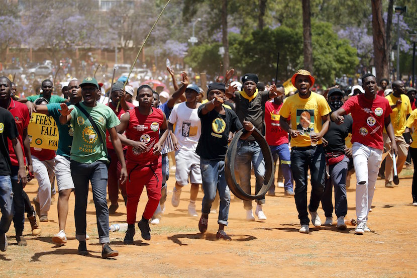 Demonstrators gesture at a photographer during a protest over planned increases in tuition fees outside the Union building in Pretoria, South Africa October 23, 2015. South African police fired stun grenades at students who lit fires outside President Jacob Zuma's offices following a week of protests, the first signs of the post-apartheid 'Born Free' generation flexing its muscle. REUTERS/Siphiwe Sibeko'Ä®