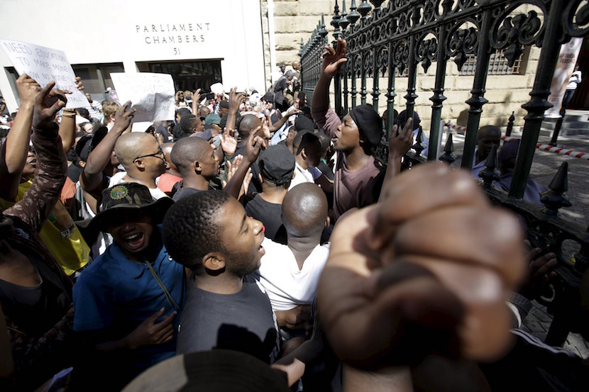 Students protest over planned increases in tuition fees outside South Africa's Parliament in Cape Town, October 21, 2015. Riot police fired tear gas and stun grenades on Wednesday at hundreds of protesting students who stormed the parliament precinct in Cape Town to try to disrupt the reading of Finance Minister Nhlanhla Nene's interim budget. REUTERS/Mark Wessels