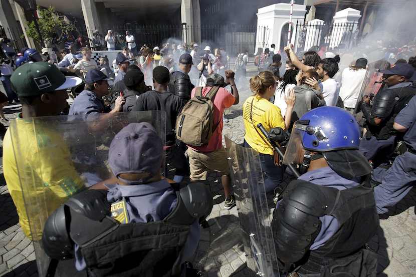 Police clash with students outside South Africa's Parliament in Cape Town, October 21, 2015. Riot police fired tear gas and stun grenades on Wednesday at hundreds of protesting students who stormed the parliament precinct in Cape Town to try to disrupt the reading of Finance Minister Nhlanhla Nene's interim budget. REUTERS/Mark Wessels