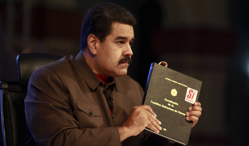 "Venezuela's President Nicolas Maduro holds a copy of the country's constitution as he speaks during his weekly broadcast ""In contact with Maduro"" in Caracas in this handout picture provided by Miraflores Palace on October 6, 2015. REUTERS/Miraflores Palace/Handout via Reuters."