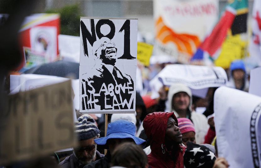 Demonstrators carry placards as they march to protest against corruption in Cape Town, South Africa September 30, 2015. REUTERS/Mike Hutchings