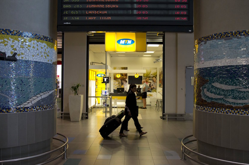 Travellers walk past an MTN telecom shop at King Shaka International Airport in Durban, South Africa, November 16, 2015. Nigeria is standing by a $5.2 billion fine imposed on MTN Group for failing to disconnect unregistered SIM cards though Monday's payment deadline may lapse while a company appeal is considered, Nigeria's telecoms regulator said. REUTERS/Rogan Ward