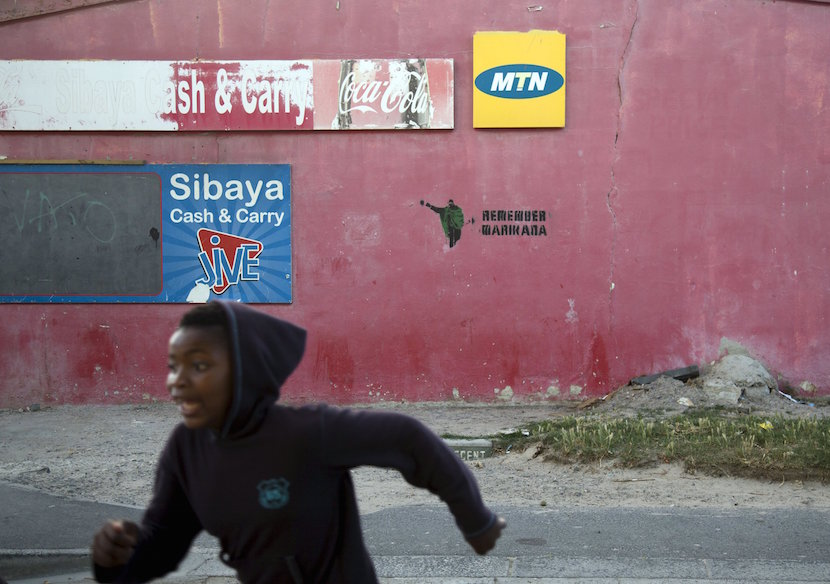 A child runs past a store with an MTN telecom logo in Gugulethu, Cape Town, November 7, 2015. REUTERS/Rogan Ward