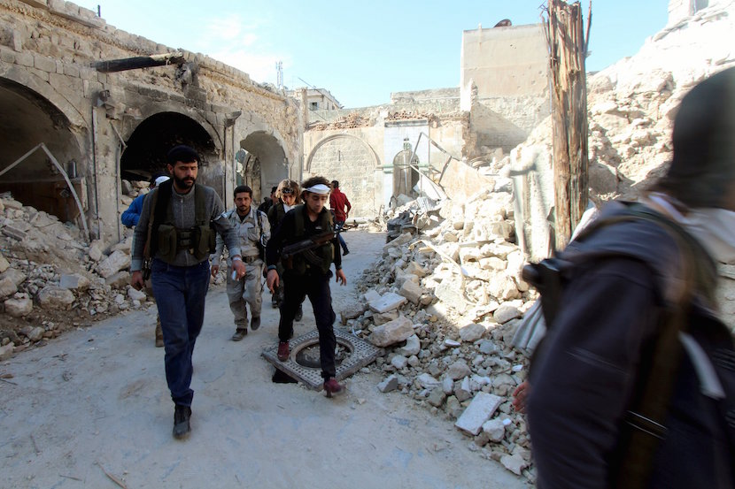 Free Syrian Amy fighters walk with their weapons prior to clashes with forces loyal to Syria's president Bashar Al-Assad during clashes in Old Aleppo, 2015. REUTERS/Abdalrhman Ismail