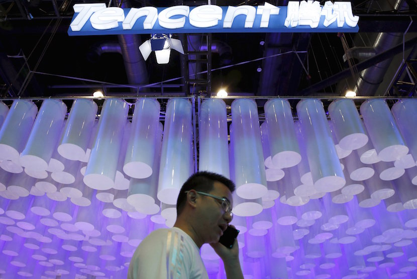 A man uses a mobile phone in front of a logo of Tencent at the Global Mobile Internet Conference (GMIC) 2015 in Beijing, China, in this April 28, 2015 file photo. REUTERS/Kim Kyung-Hoon