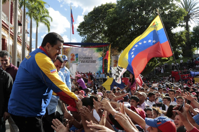 Venezuela's President Nicolas Maduro (L) greets supporters during a rally on University Student Day in Caracas, in this handout picture provided by Miraflores Palace on November 21, 2015. Venezuela will hold parliamentary elections on December 6. REUTERS/Miraflores Palace/Handout via Reuters ATTENTION EDITORS - THIS PICTURE WAS PROVIDED BY A THIRD PARTY. REUTERS IS UNABLE TO INDEPENDENTLY VERIFY THE AUTHENTICITY, CONTENT, LOCATION OR DATE OF THIS IMAGE. THIS PICTURE IS DISTRIBUTED EXACTLY AS RECEIVED BY REUTERS, AS A SERVICE TO CLIENTS. FOR EDITORIAL USE ONLY. NOT FOR SALE FOR MARKETING OR ADVERTISING CAMPAIGNS.