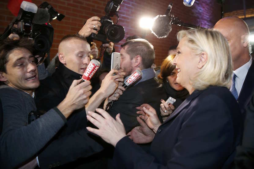 French National Front political party leader and candidate Marine Le Pen is surrounded by media as she leaves after her speech during the first round of the regional elections in Henin-Beaumont, France, December 6, 2015. REUTERS/Pascal Rossignol
