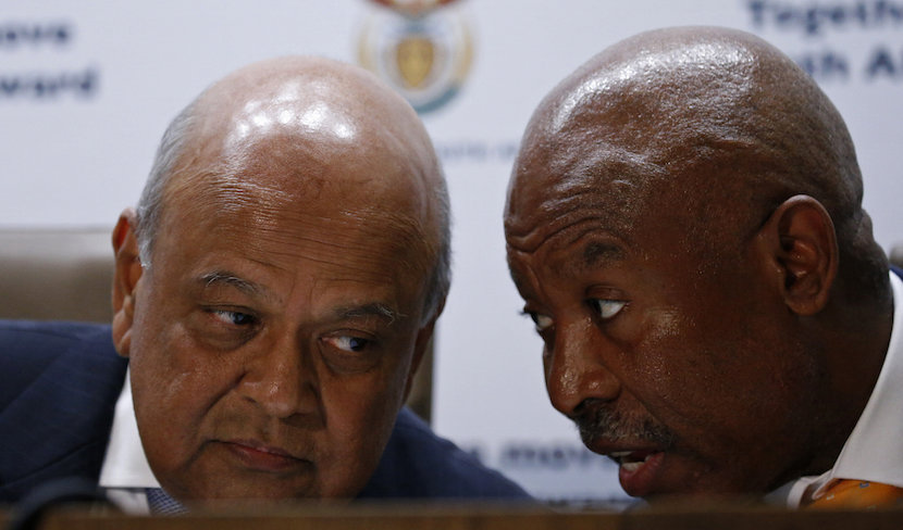 South Africa's Finance Minister, Pravin Gordhan (L) chats with Lesetja Kganyago, Governor of the Reserve Bank of South Africa, during a media briefing after Gordhan was reappointed to the position on Sunday night by President Jacob Zuma, in Pretoria, South Africa December 14, 2015. REUTERS/Siphiwe Sibeko
