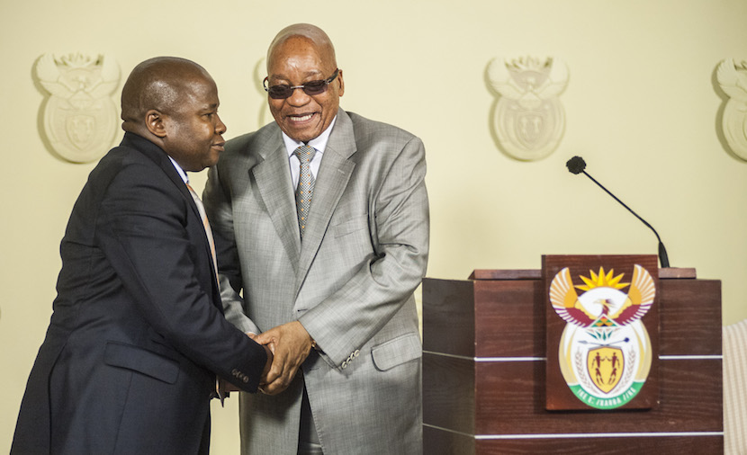 File Photo: David van Rooyen, South Africa's incoming finance minister, left, shakes hands with Jacob Zuma, South Africa's president, during his swearing in ceremony at the Union Buildings in Pretoria, South Africa, on Thursday, Dec. 10, 2015. The rand fell for a sixth day in the longest streak of losses since November 2013, stocks slid and bond prices tumbled the most on record after South African President Jacob Zuma fired Finance Minister Nhlanhla Nene and replaced him with a little-known lawmaker. Photographer: Waldo Swiegers/Bloomberg