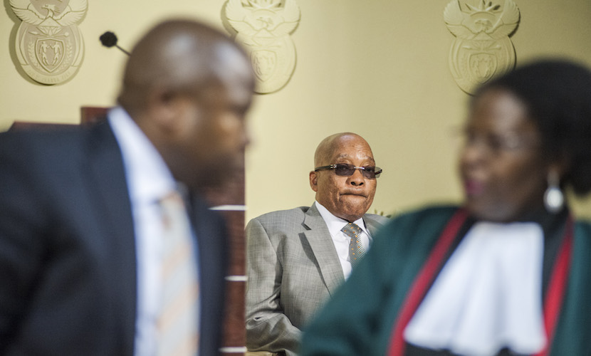 Jacob Zuma, South Africa's president, center, watches as David van Rooyen, South Africa's incoming finance minister, left, is sworn into office by Sisi Virginia Khampepe, a judge, at the Union Buildings in Pretoria, South Africa, on Thursday, Dec. 10, 2015. The rand fell for a sixth day in the longest streak of losses since November 2013, stocks slid and bond prices tumbled the most on record after South African President Jacob Zuma fired Finance Minister Nhlanhla Nene and replaced him with a little-known lawmaker. Photographer: Waldo Swiegers/Bloomberg