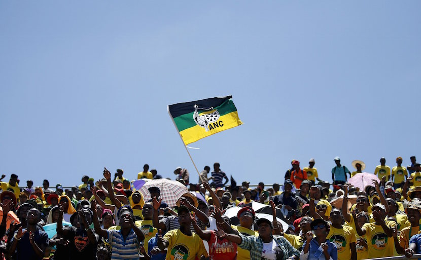 Supporters of the African National Congress (ANC) wave a party flag during the party's 104th anniversary celebrations in Rustenburg, South Africa January 9, 2016. REUTERS/Siphiwe Sibeko