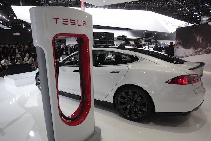 A Tesla S electric car and a charging station are displayed during the press preview day of the North American International Auto Show in Detroit