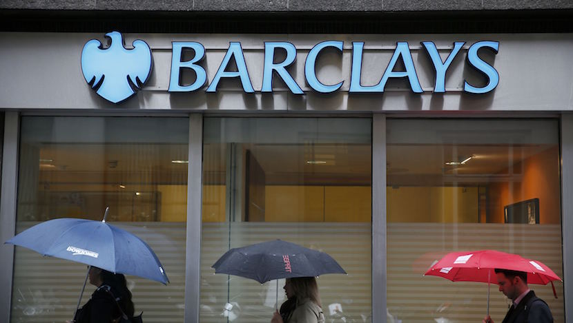 Pedestrians shelter under umbrellas as they walk past a Barclays bank branch in central London, in this file photograph dated May 8, 2014. Barclays Plc is to exit its business in Africa as part of plans to simplify the group and boost shareholder returns after reporting on March 1, 2016 a 2 percent fall in full-year profit. REUTERS/Stefan Wermuth/files