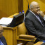 Pravin Gordhan, South Africa's finance minister, right, sits beside Jacob Zuma, South Africa's president, left, before delivering his 2016 budget speech to parliament in Cape Town, South Africa, on Wednesday, Feb. 24, 2016. Gordhan stuck to a pledge to bring down the budget deficit, targeting civil-servant jobs and increasing wealth taxes to stave off a credit-rating downgrade to junk. Photographer: Halden Krog/Bloomberg *** Local Caption *** Pravin Gordhan; Jacob Zuma