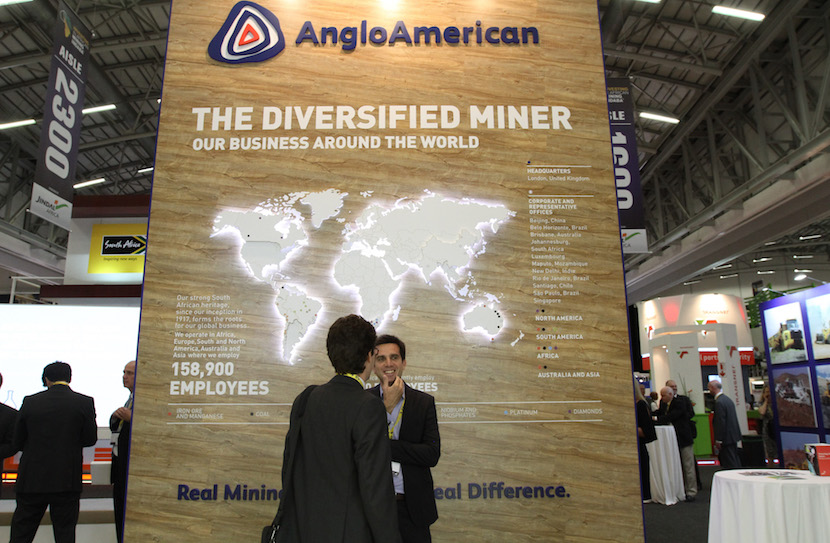 Attendees stand in front of a promotional sign for the Anglo American Plc mining company at the 20th annual Investing in African Mining Indaba in Cape Town, South Africa, on Tuesday, Feb. 10, 2015. Mining companies in South Africa risk missing output targets because of the largest power-plant breakdowns in three years, the biggest mines lobby said in Jan`. Photographer: Dean Hutton/Bloomberg