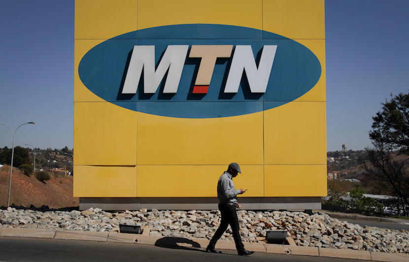 A pedestrian checks his mobile handset as he passes a giant logo outside the headquarters of MTN Group Ltd. in Johannesburg, South Africa, on Friday, Aug. 2, 2013. MTN, Africa's largest wireless operator, said first-half headline earnings per share would be 20 percent to 25 percent higher following a foreign currency exchange boost. Photographer: Nadine Hutton/Bloomberg