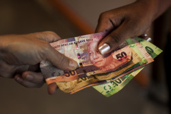 South African money (Rand) banknotes sit in this arranged photograph in Pretoria, South Africa, on Monday, Dec. 14, 2015. South Africa's government was left trying to shore up credibility after President Jacob Zuma's debacle over who should run the finance ministry called into question his ability to oversee the economy. Photographer: Waldo Swiegers/Bloomberg