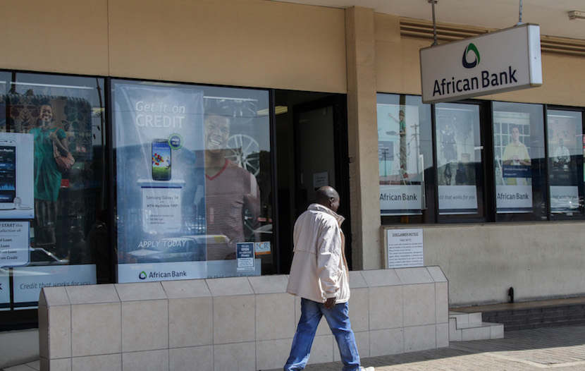 A pedestrian passes an African Bank branch, a unit of African Bank Investments Ltd. (Abil), in Johannesburg, South Africa, on Wednesday, Aug. 13, 2014. African Bank Investments Ltd., the failed South African lender being rescued by the central bank, needs to attract depositors to finance lending as risks increase that equity and bond investors will shun it after losses. Photographer: Dean Hutton/Bloomberg