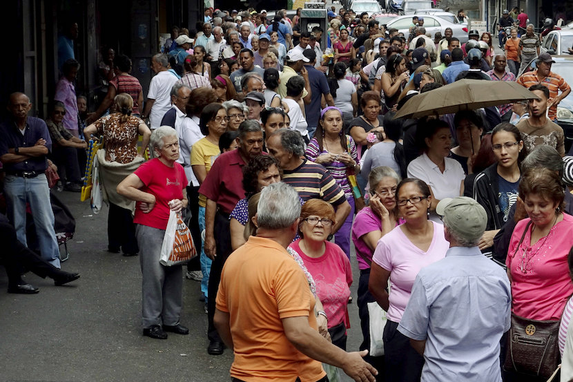 People queue to try to buy basic food