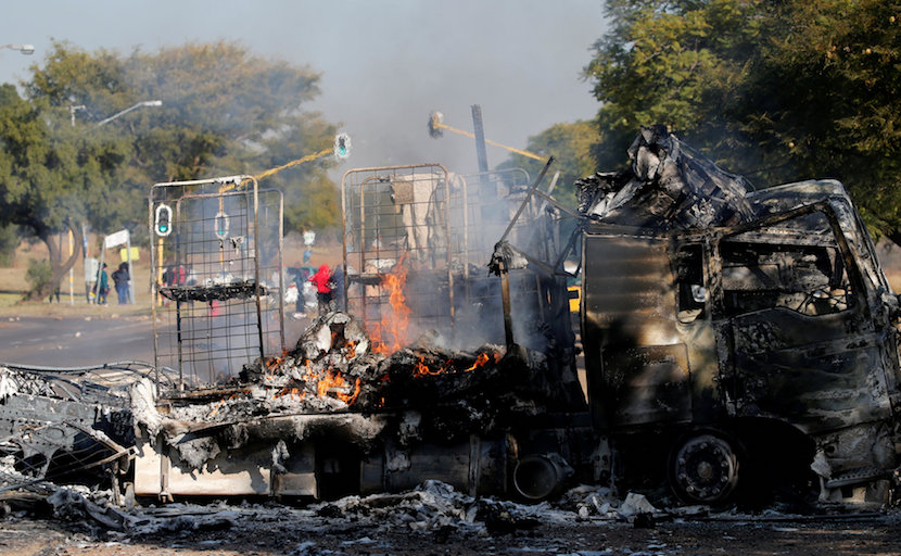 Locals walk past a shell of a burnt out truck used to barricade roads by protesters in Atteridgeville a township located to the west of Pretoria, South Africa June 21, 2016. REUTERS/Siphiwe Sibeko