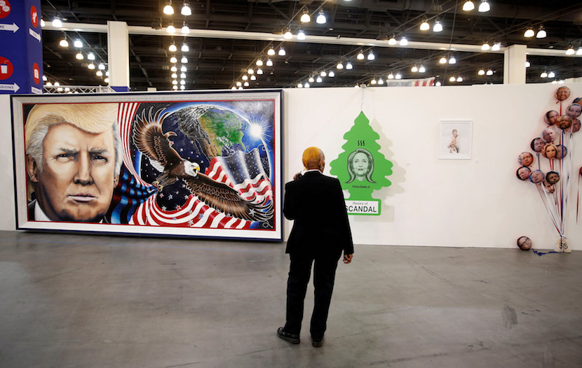 """A security guard stands in front of artwork depicting Presidential candidates including Donald Trump, Hillary Clinton, and Rick Perry during the """"Politicon"""" convention in Pasadena, California, U.S. June 25, 2016. REUTERS/Patrick T. Fallon"""