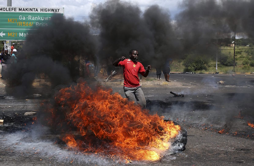 A protester reacts in front of a burning tyre as he takes part in a service delivery protest in Mabopane, in the North West province February 7, 2014. REUTERS/Siphiwe Sibeko (SOUTH AFRICA - Tags: POLITICS CIVIL UNREST TPX IMAGES OF THE DAY)