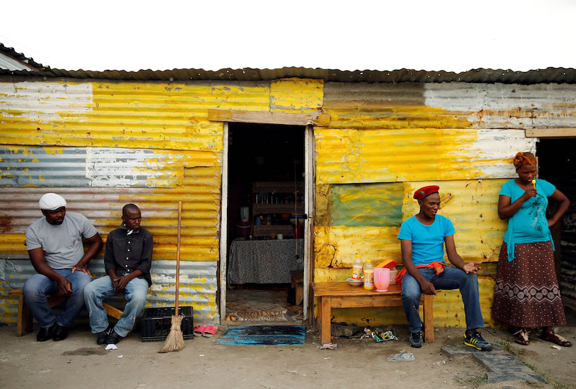 Members of a mining community sit outside a shack in Nkaneng township, Marikana's informal settlement, in Rustenburg, South Africa, April 1, 2014. REUTERS/Siphiwe Sibeko/File Photo