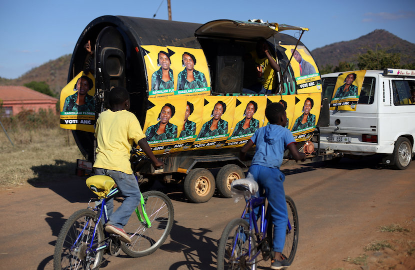 Boys ride their bicycles behind a trailer with ANC posters of a local ward councilor ahead of tommorow's local munincipal elections in Vuwani, South Africa's northern Limpopo province. REUTERS/Siphiwe Sibeko