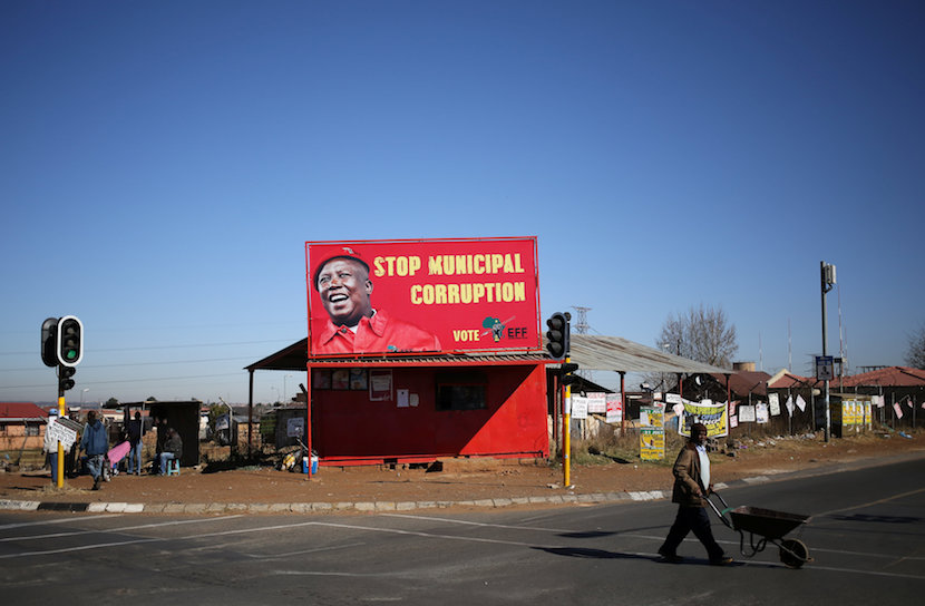 A man pushes a wheelbarrow past a billboard of the Economic Freedom Fighters (EFF), which is led by Julius Malema, in Soweto, South Africa, 2016. REUTERS/Siphiwe Sibeko