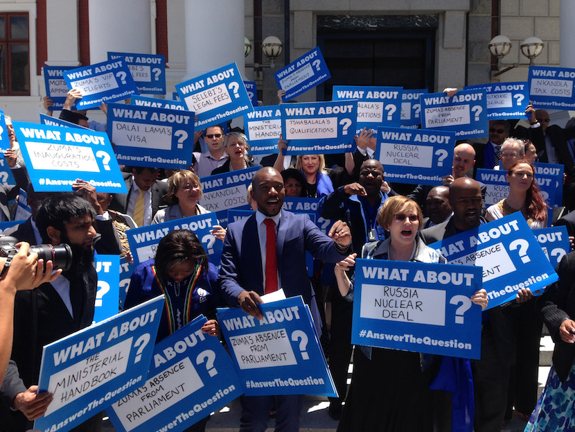 File photo: Mmusi Maimane, parliamentary leader of the Democratic Alliance, center, and Helen Zille, party leader of the Democratic Alliance, right, join Democratic Alliance lawmakers at a protest against President Jacob Zuma's failure to answer questions in the legislature, outside the National Assembly in Cape Town, South Africa. Photographer: Mike Cohen/Bloomberg
